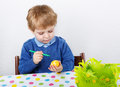 Little toddler boy painting traditional easter egg for hunt colorful action in germany eastern holiday Royalty Free Stock Photography