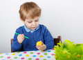 Little toddler boy painting traditional easter egg for hunt colorful action in germany eastern holiday Royalty Free Stock Photo
