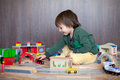 Little toddler boy playing with wooden railway indoors Royalty Free Stock Photo