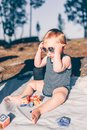 Little toddler boy putting on sunglasses on a blanket at the beach Royalty Free Stock Photo