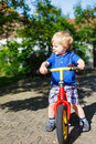 Little toddler boy riding on his bycicle in summer garden Stock Image