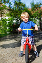 Little toddler boy riding on his bycicle in summer garden Royalty Free Stock Images