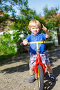 Little toddler boy riding on his bycicle in summer garden Royalty Free Stock Photos