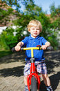 Little toddler boy riding on his bycicle in summer garden Stock Photo