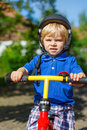 Little toddler boy riding on his bycicle in summer safety helmet garden Stock Photos