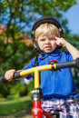 Little toddler boy riding on his bycicle in summer safety helmet garden Royalty Free Stock Images