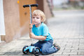 Little toddler boy riding on his bycicle in summer and scooter Royalty Free Stock Image