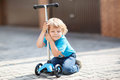 Little toddler boy riding on his bycicle in summer and scooter Stock Images