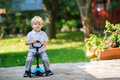Little toddler boy riding on his bycicle in summer scooter garden Royalty Free Stock Images