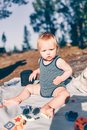 Little toddler boy sitting on a blanket at the beach Royalty Free Stock Photo