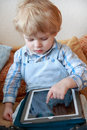Little toddler boy of two years playing with tablet pc . Royalty Free Stock Photo