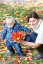 Little toddler boy and young mother in the autumn park Royalty Free Stock Photos