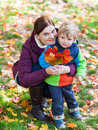 Little toddler boy and young mother in the autumn park women having fun playing with red yellow leaves Stock Photos