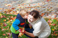Little toddler boy and young mother in the autumn park women having fun playing with red yellow leaves Stock Photo