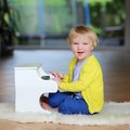 Little toddler girl plays toy piano happy child blonde curly having fun playing sitting on the sheepskin lying on the tiles floor Royalty Free Stock Photo