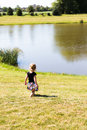 Little toddler girl walking by the pond peacefully on newly cut grass having quite time Stock Image