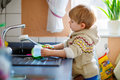 Little toddler helping in kitchen with washing dishes Royalty Free Stock Photo