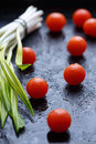 Little tomatoes on dark wet surfaces Royalty Free Stock Photo