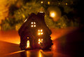 Little toy Christmas house with a burning light inside is on the table near the Christmas tree Royalty Free Stock Photo