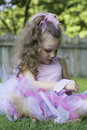 Little tutu girl a sits in the grass wearing a pink and blue a wooden fence and trees can be seen blurred in the background her Royalty Free Stock Image