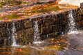 Little waterfall with stonework on creek Royalty Free Stock Photo