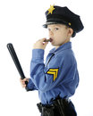 Little whistle blower cop a young elementary boy looking back at the viewer as he weilds his billy club and blows his on a white Royalty Free Stock Images