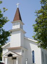 Little white church showing steeple against a blue sky with trees on each side Royalty Free Stock Photography