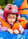 Little whitewater rafter happy girl wearing helmet sitting in a rafting boat Royalty Free Stock Image