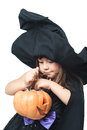 Little witch considers collected candy in pumpkin Stock Images