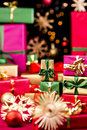 Little xmas gifts and larger presents small single colored christmas piled up between stars baubles narrow depth of field focus on Stock Photo