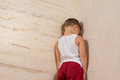 Little young boy facing wooden wall wearing white shirt and red pants Stock Image