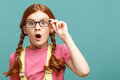 Little young girl expressing surprise great wonder close up of astonished red haired holding glasses and looking straight showing Stock Photo