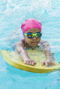 Little young girl learning swimming in a pool blue water of the Stock Images