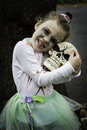Little zombie ballerina girl a dressed as a cuddles with a fake skull cute and scary at the same time black green and grey makeup Stock Photos