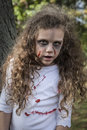 Little zombie girl a is dressed as a with scary makeup blood stained clothing and messy hair Royalty Free Stock Images