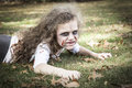 Little zombie girl a is dressed as a with scary makeup blood stained clothing and messy hair Royalty Free Stock Photos