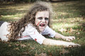 Little zombie girl a is dressed as a with scary makeup blood stained clothing and messy hair Stock Image