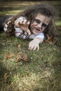 Little zombie girl a is dressed as a with scary makeup blood stained clothing and messy hair Stock Images