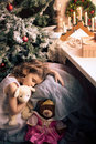Littlle girl sleeping near Christmas tree Royalty Free Stock Photo
