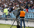 Live broadcasting camera operator on soccer field Stock Photos
