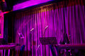 Live play stage in night pub with microphone and curtain for lve coated with pink lighting Royalty Free Stock Image