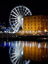Liverpool docks at night with a big wheel reflected in the river Royalty Free Stock Photo