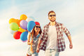 Living life to the fullest cheerful young couple holding hands and smiling while walking outdoors with colorful balloons Royalty Free Stock Images