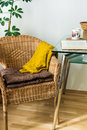 Living room interior woven rattan chair, cushions, knitted sweater, open book, tea cup, green potted plant, cozy atmosphere Royalty Free Stock Photo