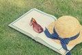 Livre et lunettes de soleil avec le chapeau de paille sur une herbe verte Photographie stock libre de droits