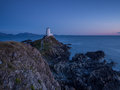 Llanddwyn lighthouse newborough anglesey cymru north wales in last light and a calm sea with rocks in the foreground Royalty Free Stock Image