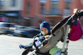 Llittle boy in a baby carriage little on the streets of the city intentional motion blur Stock Photo