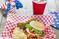 Loaded cheeseburger at a patriotic themed cookout is with ketchup mustard onion tomato and lettuce bbq it is served with potato Stock Photo