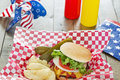 Loaded cheeseburger at a patriotic themed cookout is with ketchup mustard onion tomato and lettuce bbq it is served with potato Royalty Free Stock Photo