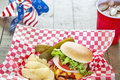 Loaded cheeseburger at a patriotic themed cookout is with ketchup mustard onion tomato and lettuce bbq it is served with potato Royalty Free Stock Image